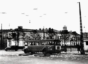 """Tyske bombemaskiner over København d. 9. april 1940. På gaden ligger nedkastede flyveblade """"OPROP"""". I baggrunden ses Palads biografen. Foto: Frihedsmuseets billedarkiv."""